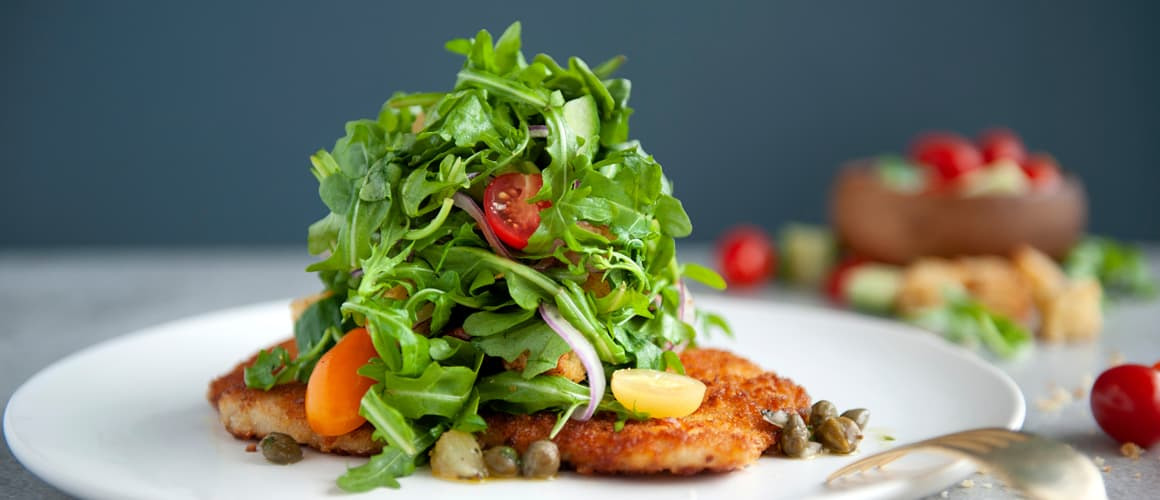 Parmesan crusted chicken breast, arugula, baby gem tomatoes, red onion, lemon caper dressing.